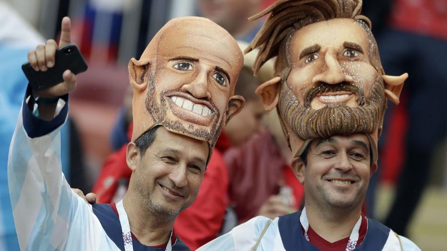 Dos hinchas argentinos en la ceremonia de inauguración del Mundial lucen las caretas de Mascherano y Messi (AP Photo/Matthias Schrader)