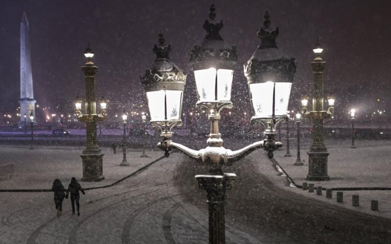 Una pareja camina por la Plaza de la Concordia cubierta por nieve (EFE/Ian Langsdon)