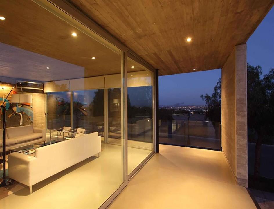 Los grandes paños de ventanales de aluminio logran una fluida relación con el paisaje exterior.  Casa S (A4 Estudio) con carpinterías Alcemar.